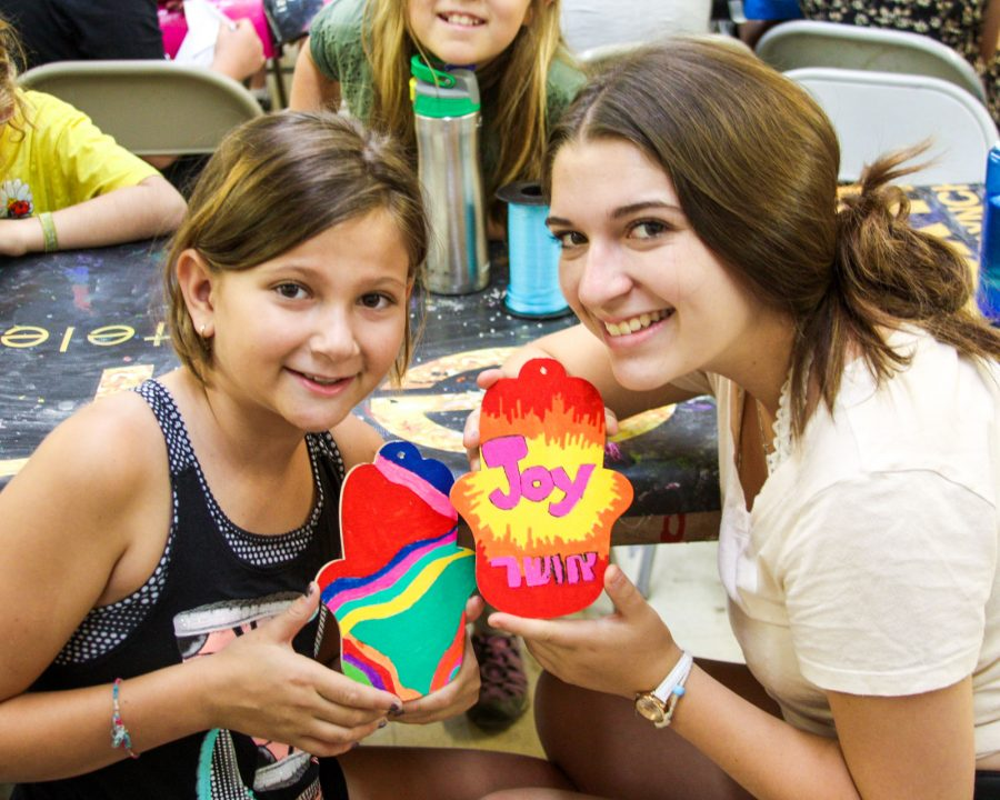 Camper and counselor making arts and crafts together