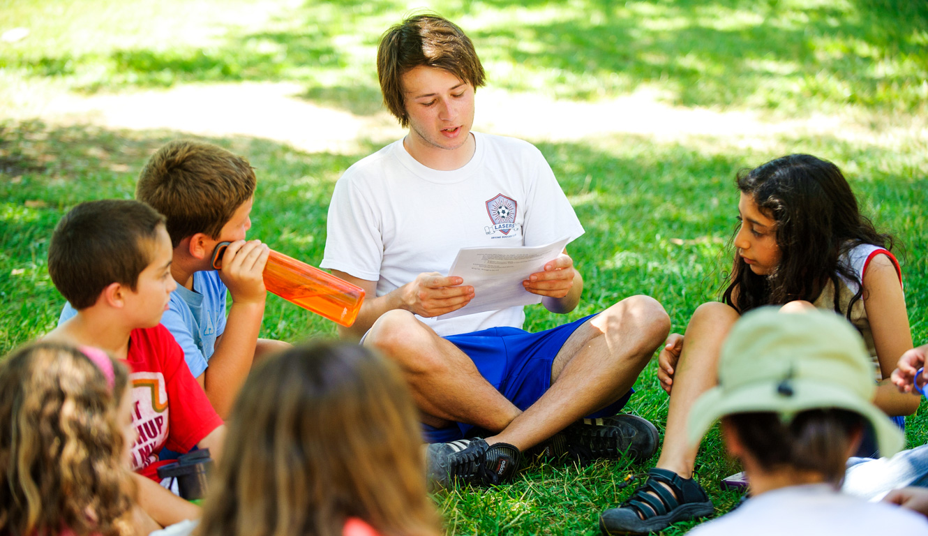 Counselor reading to campers on the grass