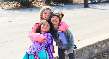 Campers in coats and hats hugging for a photo
