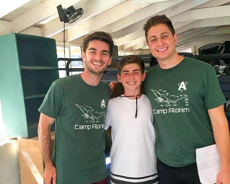 Two counselors with a camper smiling
