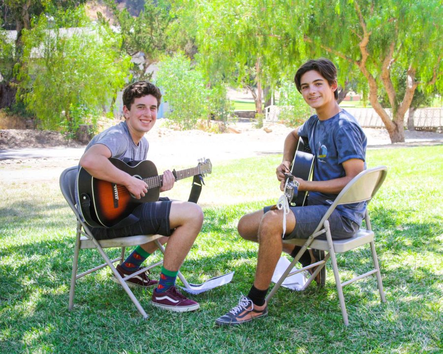 Two campers playing guitar together