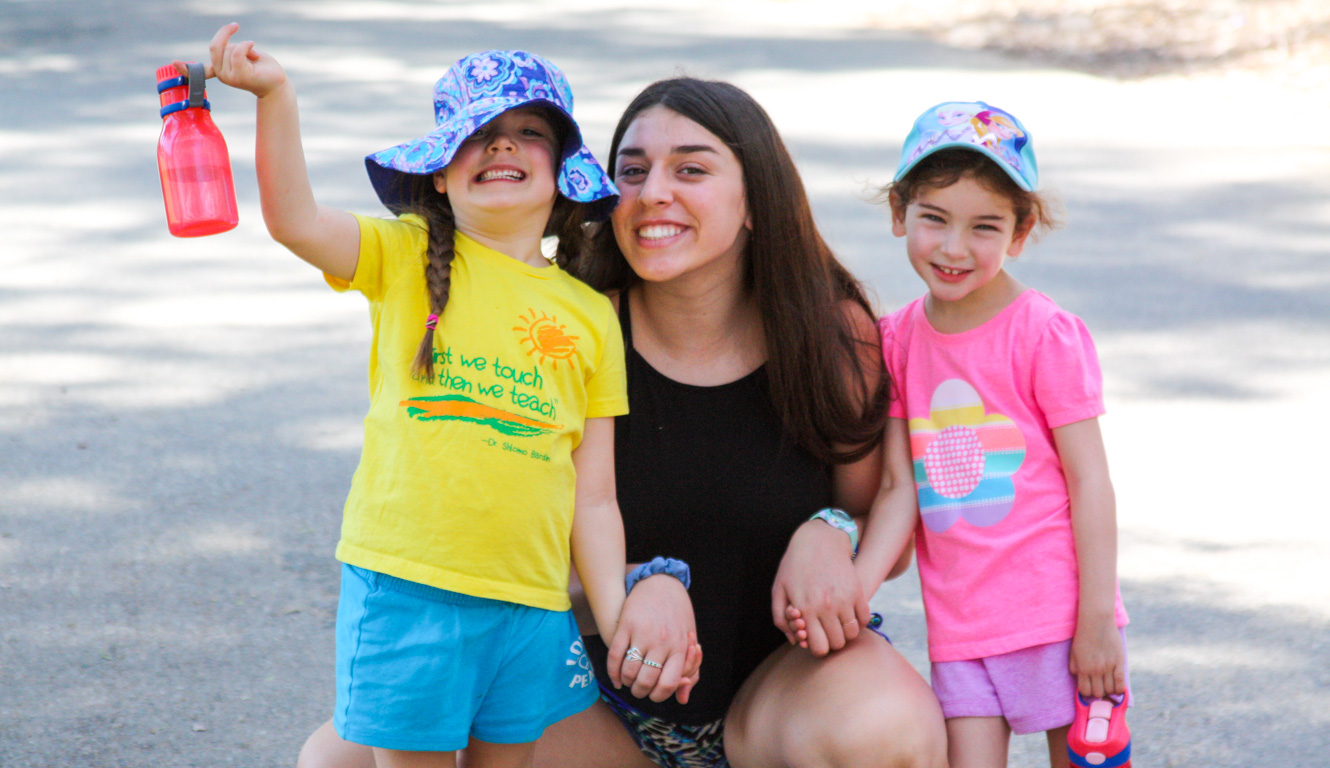Counselor smiling with campers for a photo