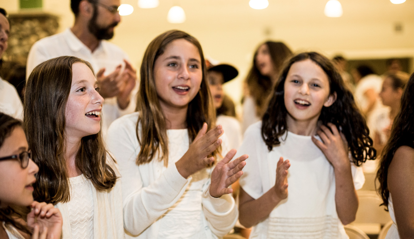 Girls clapping their hands at Shabbat