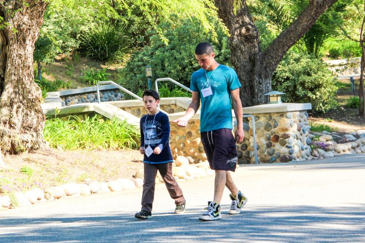 Young camper and older camper walking together on the campus