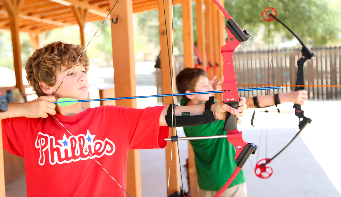 Camper pulling back the bow in an archery class