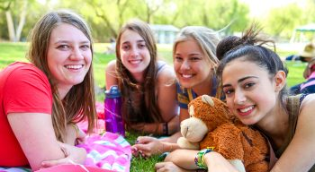 Teen campers smiling together on the grass