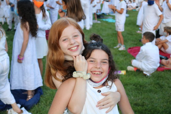 Two young camp age girls embracing and smiling